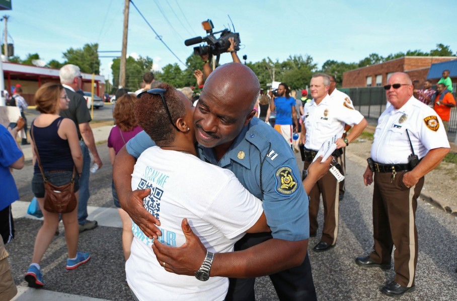 Highway Patrol Captain Ronald Johnson hugs a protester